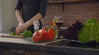 closeup details woman hands cutting vegetables for salad. On the cooking table laptop wineglass with red wine