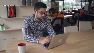 Concentrated man at the working place using computer and search information. Mixed race male wearing in casual shirt at the work. At the background two men have business meeting