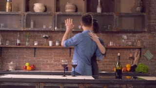 Couple in love dancing in kitchen. Happy family have fun smiling and enjoy evening in flat. Adult nice woman wearing in elegant dress. Handsome caucasian man dressed in jeans and blue shirt. On the