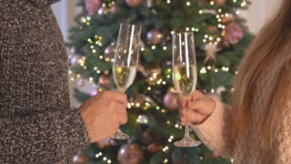couple in love holding glasses of champagne. Close up details. Man and woman flutes together in a toast chin-chin. Guy and caucasian girl with blond long hair at new year party celebrating and