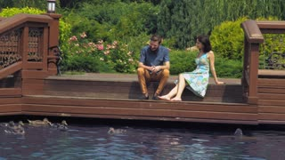 Couple in love on the romantic date in the park. Happy caucasian woman and handsome man sitting on the lake enjoy summer weekend. Attractive young girl talking smile with handsome boyfriend