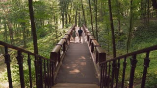 Couple in love walking in the park or forester. Happy caucasian man and woman going on the wooden bridge. Attractive female talking with handsome man on a date outdoor