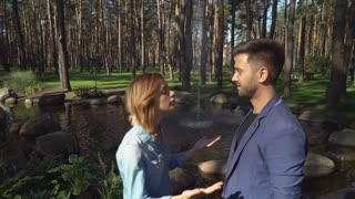Couple quarreling and reconciling at the date. Young nice pair in love arguing than kissing in the park with beautiful nature lake trees. Caucasian man and woman outdoors wearing in casual dress