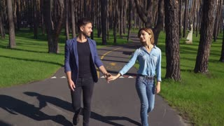 Couple young people enjoy dating in the park. Caucasian woman and man walking have fun outdoors. Pair talking smiling laughing on a date. Handsome guy holding hand attractive girl. Caucasian model