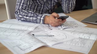 Designer using mobile phone works with plan building. take photo of sketch and send client or sharing in social net. Man hands holding smartphone texting message at the working place. On the wooden