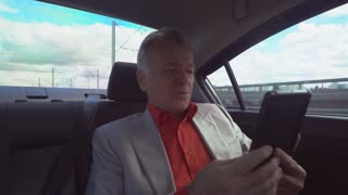 elderly man sitting on the back seat in car driving to the office. Entrepreneur holding touch screen tablet phone business partner and has friendly conversation and negotiation remote uning internet
