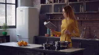 Elegant adult woman cooking and reading book in the contemporary kitchen. Young lady boiling soup at home. Caucasian woman with long hair wearing in stylish dress