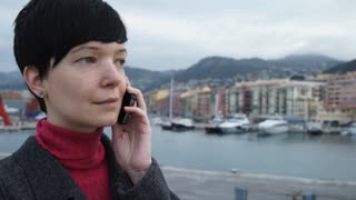Elegant young female professional standing seafront has conversation on the mobile phone. On the background harbour with ships and yachts. Girl in winter season dressed casual grey coat
