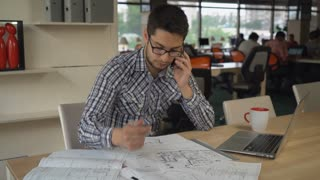 engineer sitting in at the working place on the desk blueprint. young professional man call client talking use smartphone