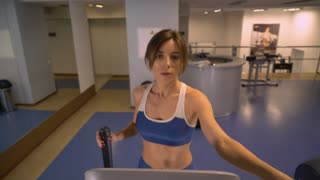 exhausted woman training on cardio machines. Caucasian girl doing exercises on elliptical trainers in gym. Attractive slim female on cross trainer. Sportswoman wearing in blue sportswear leggings and
