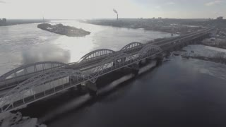 expressway bridge over the river, shooting from the air, going car, the river is almost frozen, covered with snow. Aeria 4k video