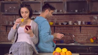 family in the evening using modern device at home. Young woman sitting on the table in kitchen. Lady wearing in sleepwear using smartphone drinking orange juice. Happy couple in love have fun at home