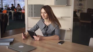 Female sitting at the personal office on shelves documents in  folders. Woman speaking on touch screen tablet. She using earphones for speaking. They discussing project. Lady with long hair smile and