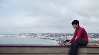 Female sitting in front of sea and slouch. Caucasian model wearing in jeans and red pullover using laptop outdoor. On the background seascape with sea beach and seafront in the marine city