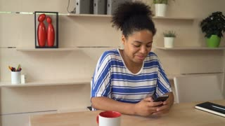 Female smiling and writing message on the smartphone. Mixed race businesswoman texting sms and read email at the working place with wooden table. Girl wearing in casual dress with blue strips