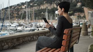 Female using app on touchscreen modern device. Caucasian model happy to talking with boyfriend at the vocation. She sitting on the bench at the seaside in mediterranean city nice provence