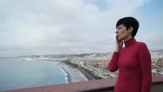 Female using mobile phone. On the background seascape with sea beach and seafront in the marine town. Caucasian girl with short black hair