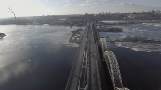 Flying over the railway bridge, at the bottom of the car ride, the river was frozen, covered with snow. Machines go to the east. Aeria 4k video