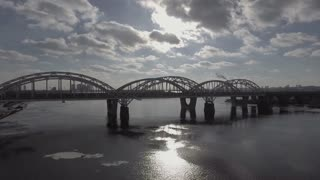 Flying over the road and rail bridge over the iron bridge. Aerial survey 4k River covered with ice