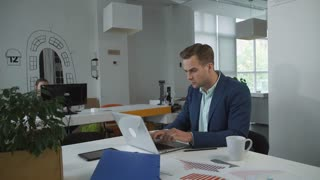Formal business meeting. Adult handsome male wearing in suit sitting at the working place. On the table computer charts and diagrams
