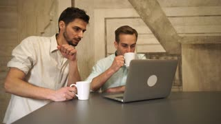 Friends drink coffee and tea consider the pros and cons of project. Mixed race man smiling. Caucasian man gesturing and point on the laptop monitor
