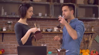 friends eating chinese food at home. Two people relishing dinner and talking smiling. Handsome man wearing in casual shirt speaking with attractive caucasian woman. Lady and guy drinking red wine in
