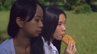 Friends smiling laughing. Young woman sharing croissant with sister. Asian girl enjoy gossip and breakfast at the open air