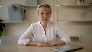 Furious business woman at the working place. Angry businesswoman sitting at the wooden desk with computer in the office. Middle aged female showing frightening symbol. Caucasian model with blonde hair