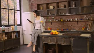 Girl drinking orange juice and reading magazine on the touch screen tablet. Attractive woman enjoy breakfast on the kitchen. Female sitting at loft room near big window at home. She using modern