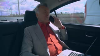 grey-haired talking on the smartphone holding laptop driving on car. Business man sitting on backseat working with pc. Caucasian male wearing in elegant suit. Through the window urban city view