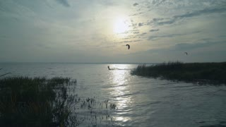 Group of active people enjoy kitesurfing on lake or river in sunset. Extreme sport in lifestyle millennium generation