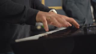 Guy playing on synthesizer close up details arms with fingers on the keyboard. Man hands play synth electronic musical instrument. concert or rehearsal rock or pop band