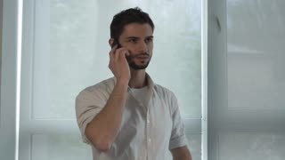 Handsome man with beard calling on the mobile phone. Indoor portrait smiling casual male with telephone