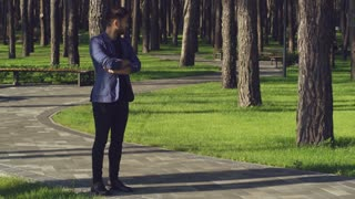 Handsome young man waiting girlfriend in park. Caucasian casual lady late on a date