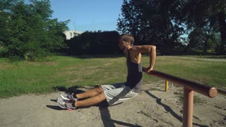 Handsome young mixed race man doing outdoors workout for arms. Attractive sportsman training forearms, biceps and triceps at the outdoor gym. Guy trains in city park at summer season. Model wearing in