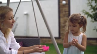 Happy caucasian woman sitting on porch swing in the garden with green grass. Smiling attractive mother play with child. Cute baby wash hands. Blonde adult female wearing in white dress smiling and