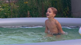 Happy child jumping in the pool. Little boy swim and play in basin at the backyard. Kid four years old enjoy laugh splash and splatter outdoors. Smiling baby laughs playing in water