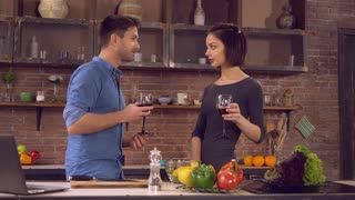 Happy couple cooking dinner on the kitchen. Young people cook salad drinking wine toasting enjoy evening talking. Beautiful couple in love on a romantic date at home