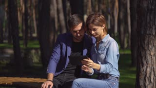Happy couple spend time at park with touch screen tablet. Handsome guy holding computer shows some funny attractive woman. Caucasian two people choose something to buy in internet. Man and girl using