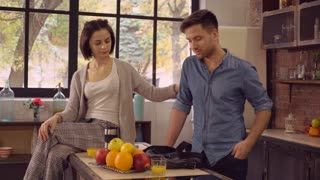 happy family on the kitchen in the morning. Young couple in love drinking orange juice at breakfast at home. Attractive woman sitting and talk with handsome man. Guy late for meeting take coffee cup