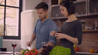 Happy family to cooking dinner at home. Couple in love talking and make salad they drinking red wine and enjoy perfect day at home. Caucasian brunette woman tearing the lettuce. Handsome smiling man