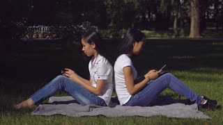 Happy friends sitting on the lawn with green grass using mobile phone. Two young asian women texting message on the smartphone. Attractive girls smiling in the park at summer season. Woman wearing in
