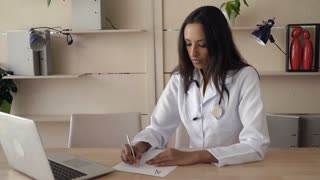 Happy indian therapist wearing in white lab coat sitting at the wooden table in office. Mixed race professional female work as physician in hospital fill recipe. Multicultural model smiling kindly on