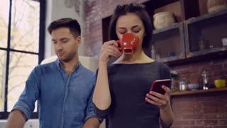 happy man and woman talking in the kitchen or office. Young people has conversation. Caucasian attractive brunette holding smartphone and drinking coffee or tea from red cup. Handsome man wearing in