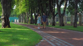 Happy man and woman walking enjoy coffee and talking. Couple friends spend free time in city park discussing something smiling and laughing. Handsome guy wearing in casual dress fashionable trousers