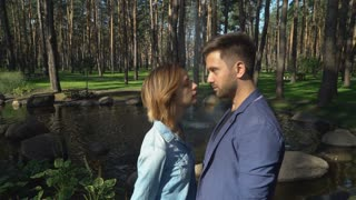Happy pair in love have fun. Cute nice woman with handsome man kissing. On the background beautiful lake with trees. Caucasian girl and attractive guy smiling dating in the city with lovely nature