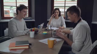 Happy professional business team at work. Smiling people working in the modern office. Attractive woman talking on the mobile phone with friendly smile. Handsome caucasian man discussing with