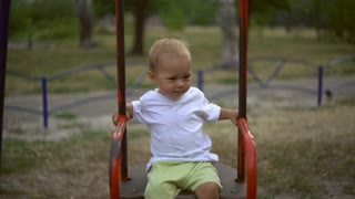 Happy smiling baby playing at the playground. Boys swinging on a red swing. Beautiful caucasian kid wearing in casual t-shirt and shorts. Infant looking at the camera and laughing playing outdoors