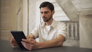 Happy smiling man talking with partner via internet. Mixed race guy using app on touch screen device. Friendly student speaking with friend. Office worker wearing in casual shirt sitting in loft