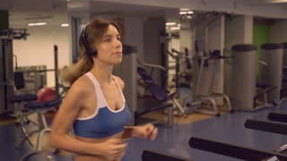 Happy woman running listening music in gum. Young girl training on a treadmill using headphones. Caucasian athlete wearing in sportswear run alone indoors
